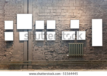 Empty frames on brown brick wall in museum