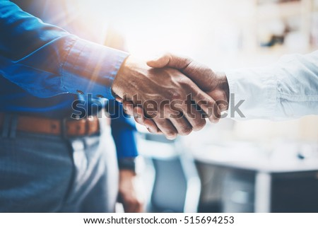 Close up view of business partnership handshake.Concept two businessman handshaking process.Successful deal after great meeting.Horizontal,flare effect, blurred background Royalty-Free Stock Photo #515694253