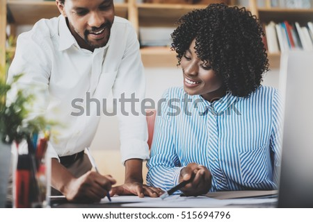 Two young coworkers working together in a modern office.Black business people discussing new startup project.Horizontal,blurred #515694796