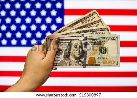 Man holding US Dollar bank note indicating market crash due to new US president with flag background #515800897