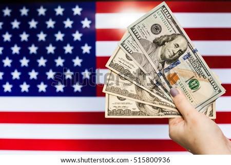 Man holding US Dollar bank note indicating market crash due to new US president with flag background #515800936