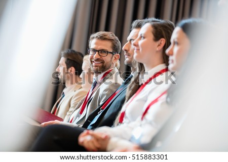 Portrait of confident businessman sitting in seminar hall Royalty-Free Stock Photo #515883301