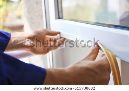 Construction worker putting sealing foam tape on window in house #515908882