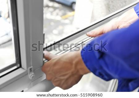 Construction worker putting sealing foam tape on window in house #515908960
