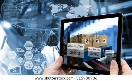 Industry 4.0,Augmented reality and smart logistic concept. Hand holding tablet with AR application for check order pick time in smart factory warehouse.Man use AR glasses and infographic background. Royalty-Free Stock Photo #515980906