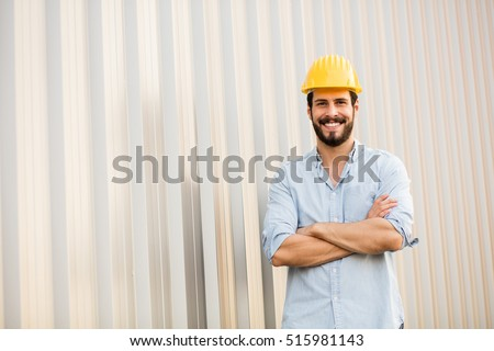 worker with yellow helmet and jeans shirt near a industrial wall #515981143