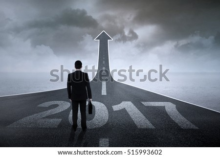 Image of male worker with a briefcase standing on a road with number 2017 and upward arrow  #515993602