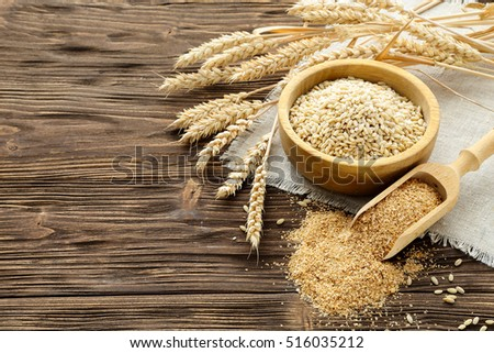 Bran, grain and wheat ears on a brown wooden table #516035212