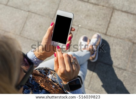 Woman standing and using smartphone
