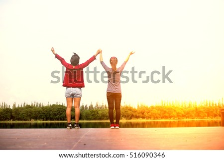 Two young beautiful woman standing by the river. Holidays. Happiness. natural beauty. #516090346
