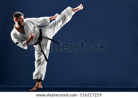 Karate man in a kimono hits foot on a blue background Royalty-Free Stock Photo #516217219