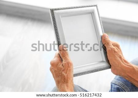Old man holding photo frame