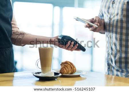 Man paying bill through smartphone using NFC technology in cafe #516245107