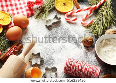 Christmas tree branch with dried oranges, cinnamon and flour on wooden table #516253420