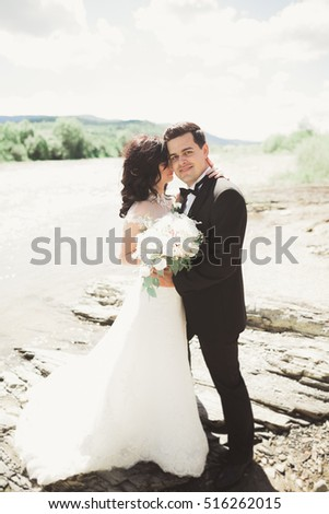 Elegant stylish happy brunette bride and gorgeous groom on the background of a beautiful waterfall in the mountains #516262015
