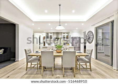 Modern dining room with hanging lamps on, there are chairs and table setup with fancy items on the wooden floor Royalty-Free Stock Photo #516468910