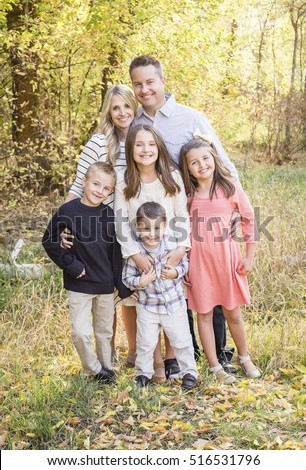 Beautiful Young Family Portrait with fall colors in the background outdoors