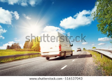 asphalt road on dandelion field with a small truck. van moving on sunny day #516537043
