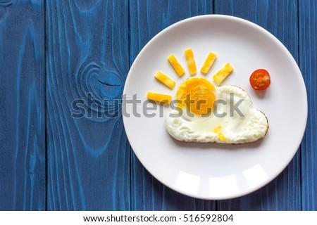 sunshine fried eggs breakfast for kid on blue background Royalty-Free Stock Photo #516592804