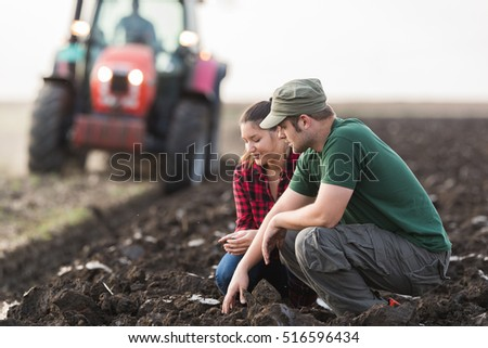 Young farmers examing dirt while tractor is plowing field #516596434
