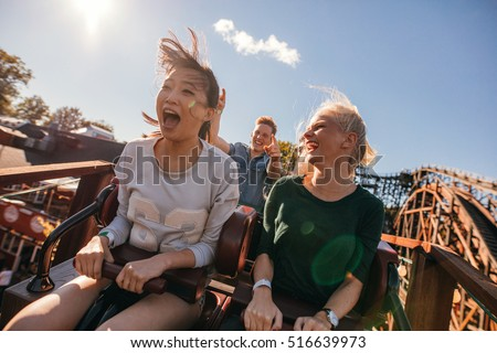 Young friends on thrilling roller coaster ride. Young women and men having fun at amusement park. Royalty-Free Stock Photo #516639973