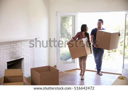 Couple Carrying Boxes Into New Home On Moving Day Royalty-Free Stock Photo #516642472