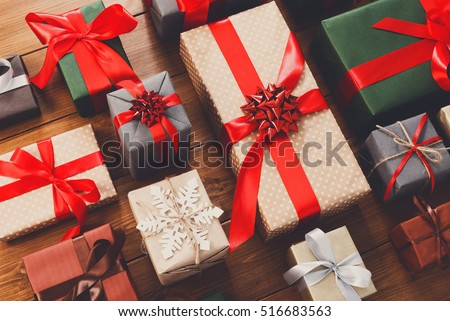 Lots of Gift boxes on wood background. Presents in craft and colored paper decorated with red ribbon bows and snowflakes. Christmas and other holidays concept. #516683563