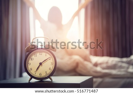 Closeup alarm clock having a good day with background happy woman stretching in bed after waking up, sunlight in morning. Royalty-Free Stock Photo #516771487