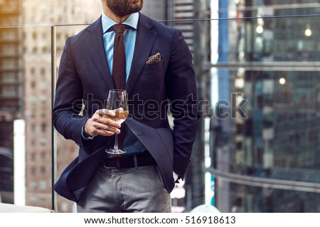 Concept photo of rich people luxury life. Adult successful elegant businessman wearing suit and drinking wine on the rooftop in luxury penthouse in New York City. Royalty-Free Stock Photo #516918613
