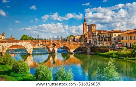 Panoramic view to Bridge Ponte Pietra in Verona on Adige river. Veneto region. Italy. Sunny summer day panorama and blue dramatic sky with clouds. Ancient european italian terracotta color houses #516926059