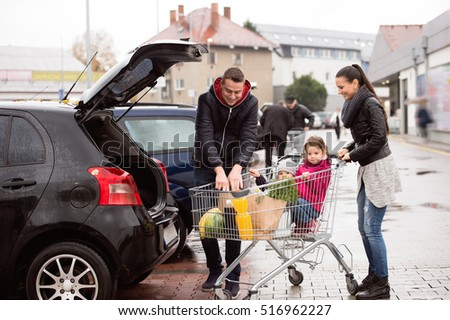 Parents pushing shopping cart with groceries and their daughters #516962227