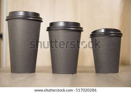 three paper Cup of black coffee on wooden background #517020286
