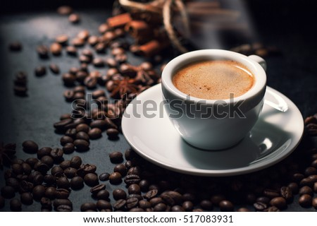 Fresh tasty espresso cup of hot coffee with coffee beans on dark background #517083931