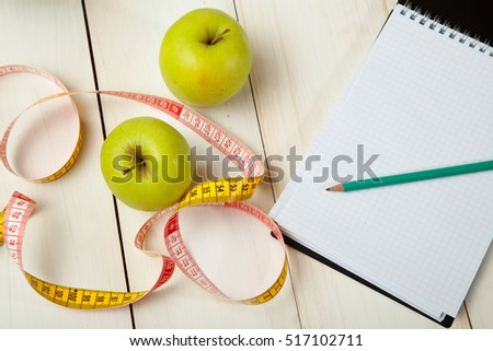 Green apple with measuring tape on white background #517102711