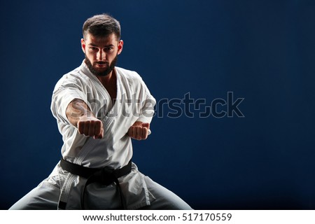 Karate man in a kimono in fighting stance on a blue background Royalty-Free Stock Photo #517170559