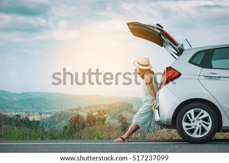 Woman traveler sitting on hatchback car with mountain background in vintage tone Royalty-Free Stock Photo #517237099