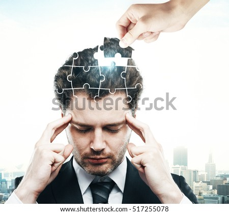 Hand adding last piece to pensive puzzle headed businessman on city background. Business challenge and solution concept #517255078