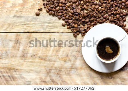 coffee beans on wooden with coffe cup table top view #517277362
