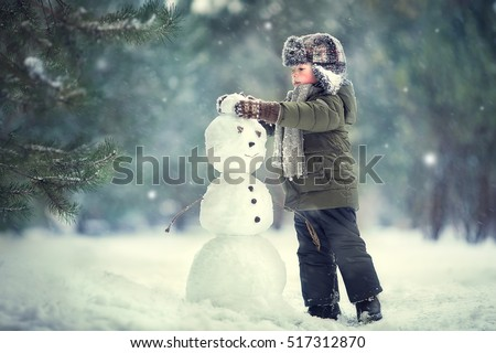 Cute little boy in earflaps hat is making a snowman. Image with selective focus and toning Royalty-Free Stock Photo #517312870