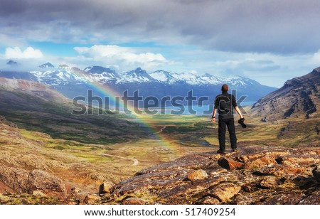 Fantastic views of the mountains and a little rain and a rainbow in Iceland. Colorful colors. Dramatic cumulus clouds. The man considers beautiful landscapes. Europe. #517409254