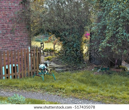 an old rustic metal rocking horse is in a green garden. Brick wall and timber fence behind #517435078