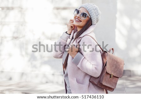 Young stylish woman wearing pink warm coat, pants and handbag walking in the city street in cold season. Winter fashion, elegant look, outfit in pastel colors. Plus size model. #517436110