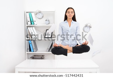Young calm brunette business woman levitating above office desk and meditating in lotos position with flying objects around #517442431