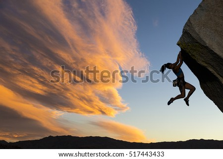 Female climber dangles from the edge of a challenging cliff. #517443433