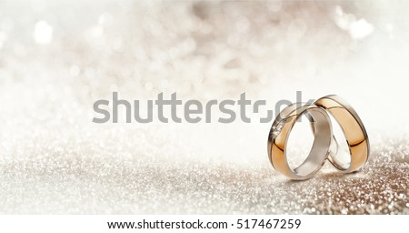Panoramic banner of two upright gold wedding bands symbolic of love and romance on a textured glitter background with copy space for your greeting or congratulations #517467259