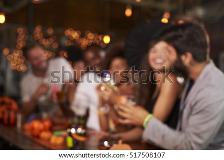 Young adults socialising at a party in a bar, defocussed #517508107