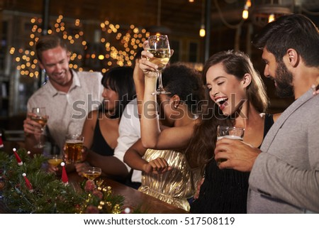 Woman raising a glass at a Christmas party in a bar #517508119