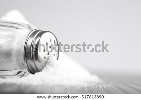 glass salt shaker on gray table and white background for text Royalty-Free Stock Photo #517613890