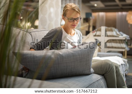 Pretty, young woman choosing the right furniture for her apartment in a modern home furnishings store (color toned image; shallow DOF) #517667212