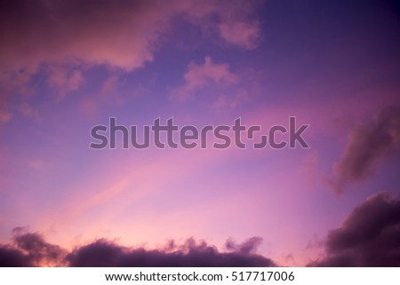 Clouds at sunset  in tropical Broome, North Western Australia  are beautifully hued with soft salmon pink, grey and  pale blue tones as the hot sun sinks into the Indian Ocean  in summer #517717006